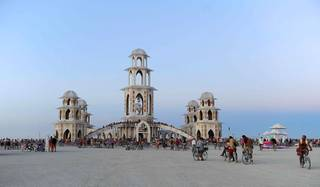 In this Aug. 30, 2011, photo, people gather at the temple during the Burning Man festival in northern Nevada. The temple,  built for the festival in downtown Reno, was hauled in pieces earlier this month on 20 flatbed trucks to the Black Rock desert, where about 140 volunteers from around the world helped with construction. During the festival, which began Monday, people can leave messages and mementos at the temple to help them move on after the loss of a close family member or friend. The temple will be burned on the morning of Sept. 4, which is the day after