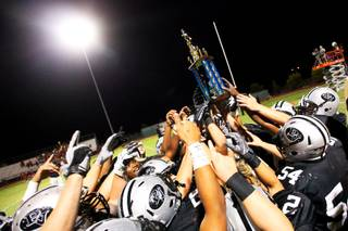 Palo Verde High football players celebrate their 14-7 victory against visiting Arbor View Thursday, Sept. 1, 2011, by holding up the Thursday Night Lights trophy. The winner of the Thursday television game each week receives a trophy.