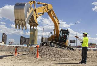 Heavy equipment instructor Ruben Segura directs Daniel De La Garza of Austin, Texas, at picking up a basketball with an excavator Monday, Aug. 29, 2011, in Las Vegas.