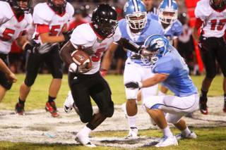 Las Vegas running back Farrell Victor stiff arms Centennial defensive player  during their game Friday, September 2, 2011 at Centennial High School. .  Las Vegas came from behind for a 24-21 win.