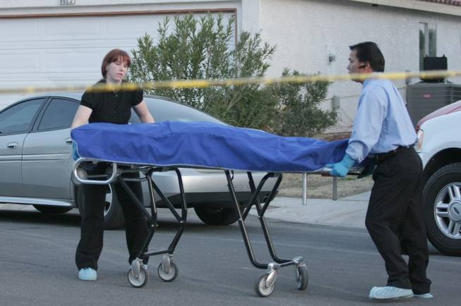 In this 2009 file photo, officials with the Clark County coroner's office remove bodies from the scene of what authorities suspected to be a murder-suicide. Reality TV producers want to pay the county $5,000 per episode to follow coroner's office employees on their jobs.
