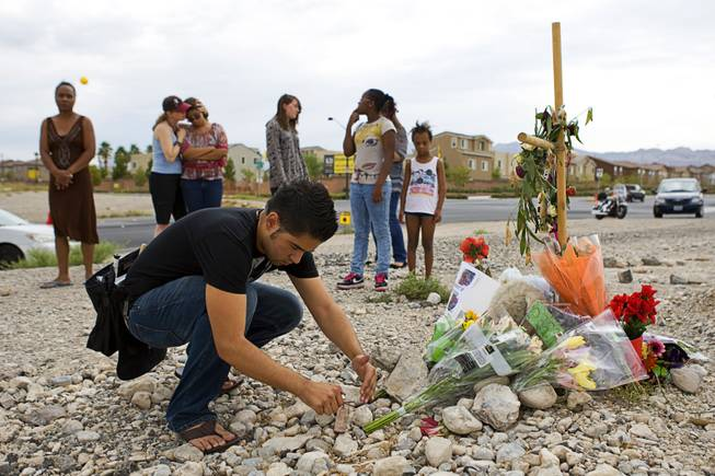 Francisco Servin lights a candle at a memorial for 15-year-old Alyssa Otremba near Grand Teton Drive and Tee Pee Lane Monday, September 5, 2011.
