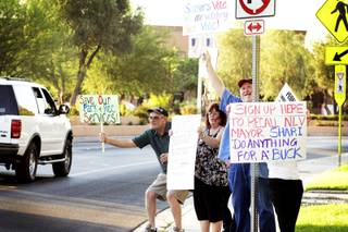 Residents hold up signs to motorists passing on Civic Center Drive urging the recall of North Las Vegas Mayor Shari Buck as they protest in front of the North Las Vegas City Hall on Wednesday, Sept. 7, 2011.