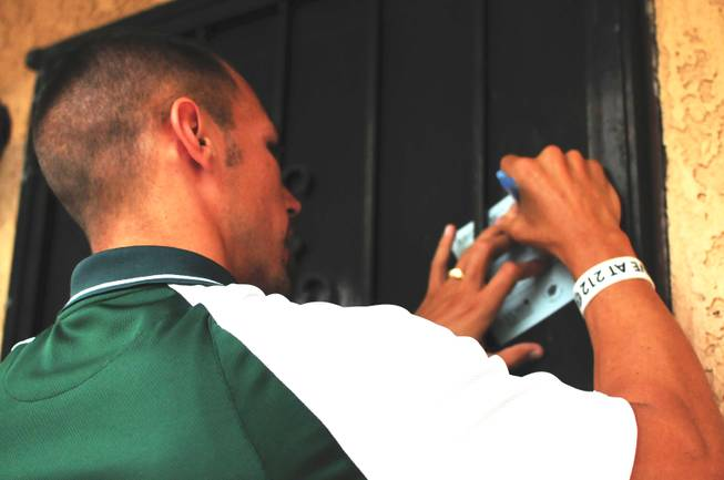 "Mojave High School Principal Antonio Rael leaves a calling card on the door of an at-risk student during the Clark County School District's ""Reclaim Your Future"" event on Saturday, Sept. 10, 2011. The volunteer event encourages at-risk, ""non-returning"" students to come back to school and graduate."