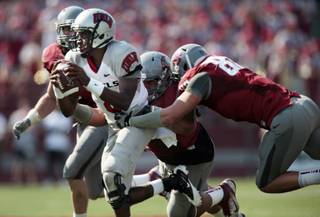 Washington State defensive end Travis Long, right, and defensive tackle Kalafitoni Pole, center, sack UNLV quarterback Caleb Herring (8) as linebacker Alex Hoffman-Ellis, left, pursues during the first half of their NCAA college football game on Saturday, Sept. 10, 2011, in Pullman, Wash.