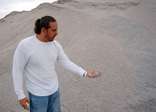 Tommy Fisher, of Fisher Sand & Gravel, holds a handful of gravel at the Sloan Quarry Wednesday, September 14, 2011.  Fisher mixes crumb rubber from old tires with oil and rock to make the rubberized asphalt that is being used in the repaving of Interstate 15.
