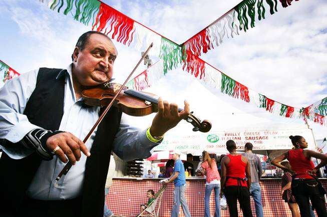 Violin player Sandor Beke entertains the crowds near the food booths during the San Gennaro Feast at the Rio on Wednesday, Sept. 14, 2011.