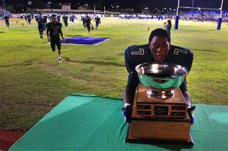 Green Valley running back Aaron Love grabs the Henderson Bowl trophy after their annual game against Basic Friday, September 16, 2011. After three consecutive losses to Basic, Green Valley won the game 36-33.