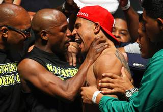Undefeated welterweight boxer Floyd Mayweather Jr., left, grabs the throat of WBC welterweight champion Victor Ortiz as they face off during an official weigh-in at the MGM Grand Garden Arena Friday, September 16, 2011. Mayweather will challenge Ortiz for the title at the arena Saturday.
