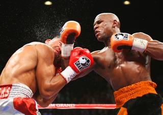WBC welterweight champion Victor Ortiz, left, takes a punch from Floyd Mayweather Jr. during their title fight at the MGM Grand Garden Arena on Saturday, Sept. 17, 2011.