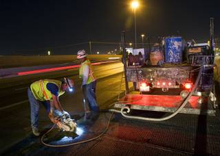 Higinio Arrenondo and Patrice Whitlaw prepare a section of road for a patch during resurfacing of Interstate 15 between Tropicana Avenue and Charleston Boulevard on Monday, Sept. 19, 2011.