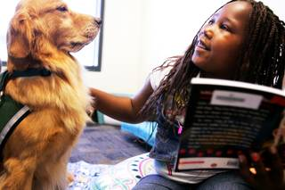 Caitlyn Cooks reads to Peaches as part of the program Reading With Rover at Gibson Library in Henderson on Tuesday, Sept. 20, 2011.