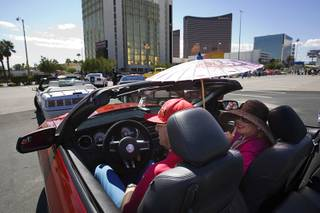 Art Greenberg and Febe Soriano wait for the start of the Barrett-Jackson Road Rally car parade Wednesday, Sept. 21, 2011. Greenberg had the convertible top down on his 2011 Mustang GT, but Soriano protected herself with a hat and parisol.