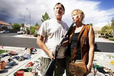 Steve Henderson with a black powder muzzleloader gun and his wife, Nellie, with a buckskin vest for sale at their driveway in Henderson on Saturday, Sept. 24, 2011.