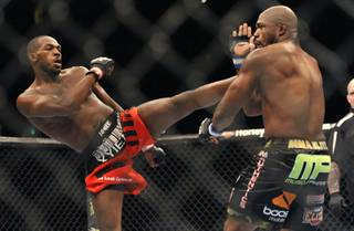 Jon Jones, left, of Endicott, N.Y., gets in a kick to the head of Rampage Jackson, of Irvine, Calif., during the first round of their UFC light heavyweight title bout, Saturday, Sept. 24, 2011, in Denver.