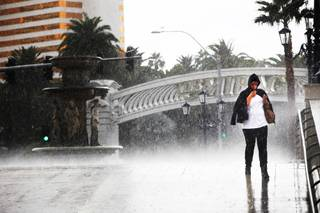 A woman walks during a downpour on the Strip outside the Venetian in Las Vegas on Monday, Oct. 3, 2011.