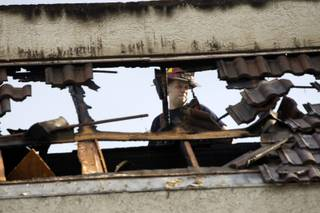 A firefighter looks over a hole in a mansard roof after lightning struck an office building at 2785 E. Desert Inn Road on Monday, Oct. 3, 2011. City of Las Vegas and Clark County fire units responded to the fire.