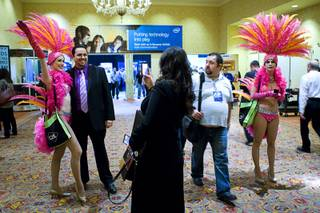 A show attendee has his photo taken with a showgirl during the first day of the Global Gaming Expo (G2E) convention at the Sands Expo Center Tuesday, Oct. 4, 2011.