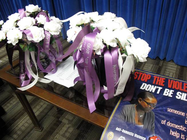 Thirty flowers, each representing a domestic violence homicide victim, fill vases at a ceremony to honor victims and kick off Domestic Violence Awareness Month. The 30 homicide victims died between July 1, 2010, and June 30, 2011.