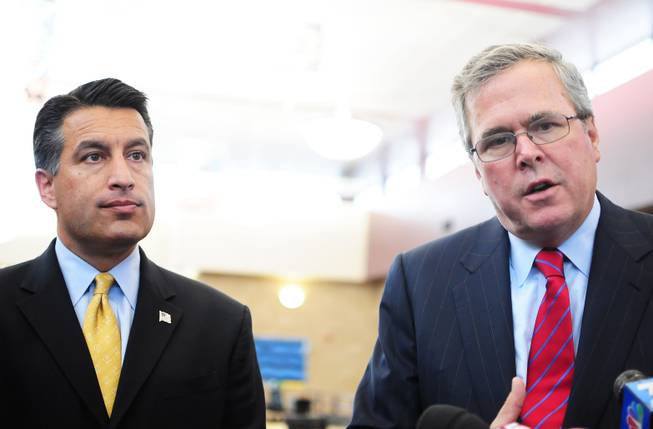 Gov. Brian Sandoval and former Florida Gov. Jeb Bush talk with media after their tour of Andre Agassi College Preparatory Academy in the northern Las Vegas Valley on Wednesday, Oct. 5, 2011.