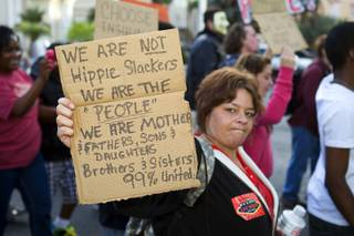 A woman who identified herself as Janelle K. holds up a sign during an Occupy Las Vegas protest on the Las Vegas Strip Thursday, Oct. 6, 2011. The protest was held in solidarity with Occupy Wall Street demonstrations in New York and in other parts of the U.S.
