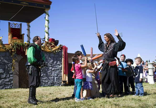 """Capt. Griffin"" (Tawn Jones) enlists children from the audience to subdue his partner ""Guido"" (Jeff Winters) during a ""Nature of Mercy"" performance at the Age of Chivalry Renaissance Festival in Silver Bowl Park on Sunday, Oct. 9, 2011."
