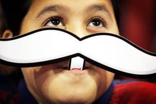 Leonardo Jalion, a fourth-grader at Paradise Elementary School, wears a Rebel mustache during the Rebel Reading Challenge Kickoff for fourth- and fifth-grade students at the Thomas & Mack Center in Las Vegas on Monday, Oct. 10, 2011.