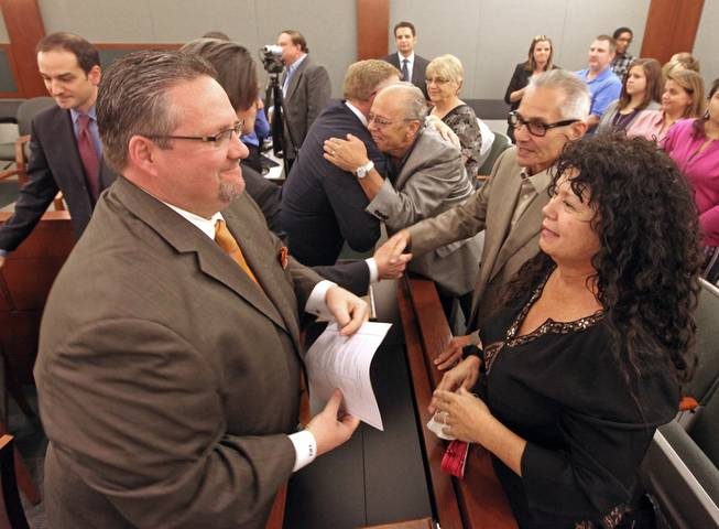 Plaintiff Anne Arnold (right) reacts along with attorney's Robert Adams (left) and Robert Eglet (center) hugging Anthony Devito after a jury Monday, Oct. 10, 2011, ordered three pharmaceutical companies to pay $162.5 million in punitive damages to five plaintiffs in a lawsuit that accused them of negligently distributing large vials of an anesthetic to Las Vegas clinics at the center of a 2008 hepatitis C outbreak.