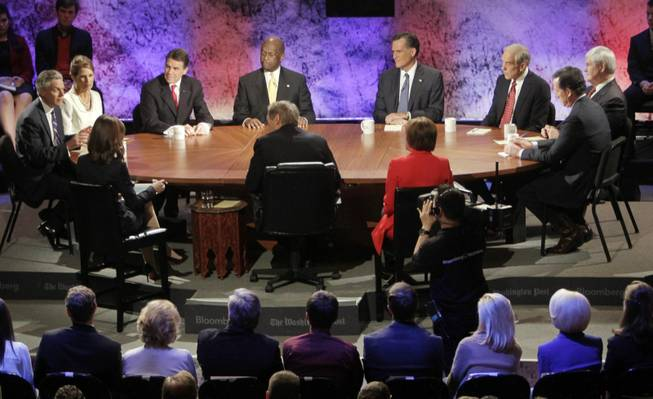 Republican presidential candidates, from left, former Utah Gov. Jon Huntsman, Rep. Michele Bachmann, R-Minn., Texas Gov. Rick Perry, businessman Herman Cain, former Massachusetts Gov. Mitt Romney, Rep. Ron Paul, R-Texas, former House Speaker Newt Gingrich and former Pennsylvania Sen. Rick Santorum are seen at the debate at Dartmouth College on Tuesday, Oct. 11, 2011, in Hanover, N.H.