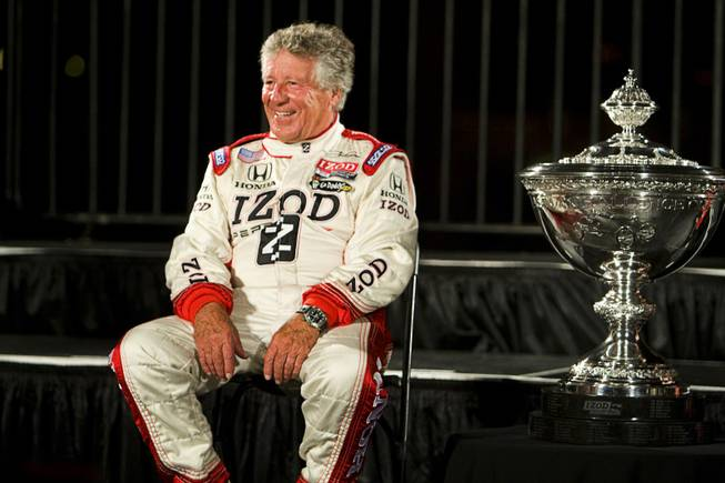 Racing legend Mario Andretti sits by the championship trophy before driver introductions in front of the Bellagio Thursday, Oct. 13, 2011. The IZOD IndyCar World Championship race will be held at the Las Vegas Motor Speedway Sunday.