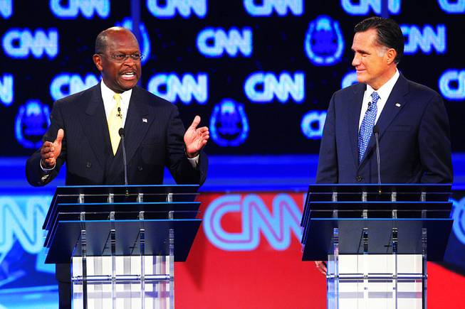 Herman Cain and Mitt Romney are seen during the GOP presidential debate sponsored by CNN on Tuesday, Oct. 18, 2011, at the Venetian.