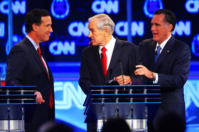 Rick Santorum, Ron Paul and Mitt Romney interact during a break in the GOP presidential debate sponsored by CNN on Tuesday, Oct. 18, 2011, at the Venetian.