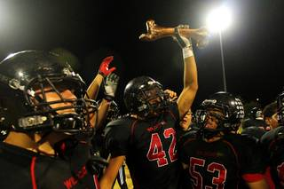 After beating Rancho 49-12, Las Vegas' Kaveo Walker holds the rivalry trophy, a bronzed cow bone, above his head Thursday, Oct.  20, 2011.