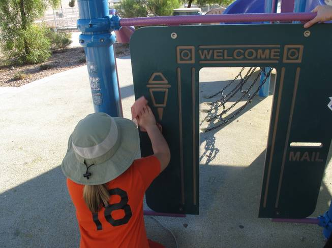 A young volunteer works to remove graffetti, gum and other marks off the playground in Sandstone Ridge Park in North Las Vegas for Make a Difference Day.