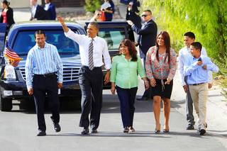 President Barack Obama walks with, from left, Jose Bonilla, Lissette Bonilla and their children Margarita Bonilla, Franco Bonilla and Mario Bonilla before Obama spoke about the American Jobs Act on Oct. 24, 2011, in Las Vegas. Obama also announced a housing initiative to help homeowners with federally guaranteed mortgages refinance their homes.