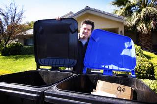 Todd Korgan stands with his new recycling and garbage bins at his home near downtown Las Vegas on Wednesday, Oct. 26, 2011.