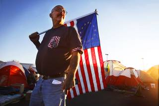Mark Andrews of Las Vegas stands with an American flag with 13 colonies at Occupy Las Vegas between Paradise Road and Swenson Street south of East Naples Drive in Las Vegas on Thursday, Oct. 27, 2011.