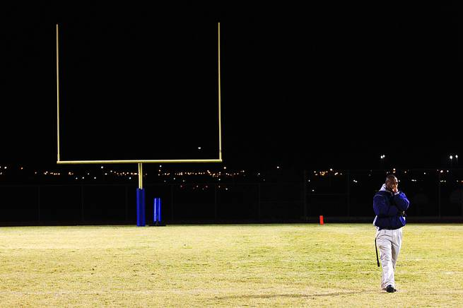 Canyon Springs coach Hunkie Cooper takes a moment to collect himself after talking to his players in the wake of their 22-21 overtime win over favored Las Vegas Thursday, Oct. 27, 2011.