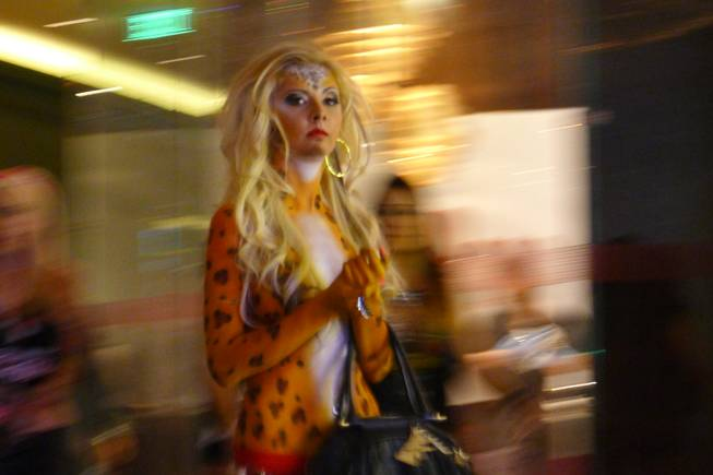 A woman dressed as a tiger clutching a purse was among the costumed creatures cavorting Saturday night outside the Chandelier Bar on the Las Vegas Strip.
