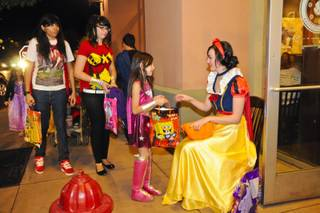 Linzie Lee hands out candy to trick-or-treaters at The District on Halloween night Monday, Oct. 31, 2011.