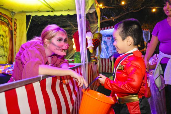 Nicole Truex, dressed as a carnival freak named Pig Girl, hands out candy to a trick-or-treater at The District on Halloween night Monday, Oct. 31, 2011.