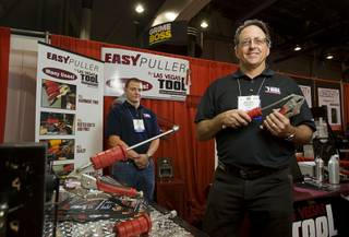 General contractor Mark Giberti, right, poses with the EasyPuller during the Specialty Equipment Market Association (SEMA) trade show at the Las Vegas Convention Center, Nov. 2, 2011. His son Jason is at left. Giberti invented the EasyPuller for his own use but never had time to develop the product until the economic downturn, he said. The EasyPuller by Las Vegas Tool combines locking pliers with a slide hammer.
