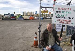 Henri Palnar holds a sign on Swenson Street in front of the Occupy Las Vegas site near Tropicana Avenue Thursday, Nov. 3, 2011.