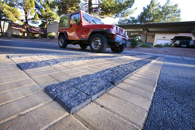 A resident drives over recently installed rumble strips in Quail Estates West community off Valley View Boulevard near Sahara Avenue Monday, October 7, 2011. The strips can be placed as a warning before a cross walk or in a congested area to remind people to watch their speed.