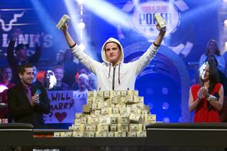 Pius Heinz of Germany holds up stacks of cash after defeating Martin Staszko of the Czech Republic to win the championship bracelet and $8.7 million in first-place prize money during the World Series of Poker Main Event early Wednesday morning, Nov. 9, 2011, at the Rio. In the background are 2010 winner Jonathan Duhamel and ESPN reporter Kara Scott.
