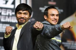 Filipino boxer Manny Pacquiao, left, and Mexican boxer Juan Manuel Marquez pose during a news conference at the MGM Grand Wednesday, November 9, 2011. Pacquiao will face Marquez for the third time when he defends his WBO welterweight title against Marquez at the MGM Grand Garden Arena Saturday.