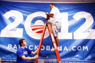 Field organizer Tyson Megown, left, and regional field director Steve Sisneros hang a gigantic sign inside the new Organizing for America-Nevada office in Henderson Thursday, Nov. 10, 2011.