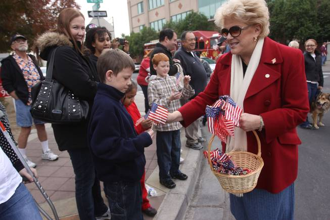 Las Vegas Mayor Carolyn Goodman hands a flag to Taylor Cochran, 11, during the annual Veterans Day parade on 4th Street in downtown Las Vegas on Friday Nov. 11, 2011.