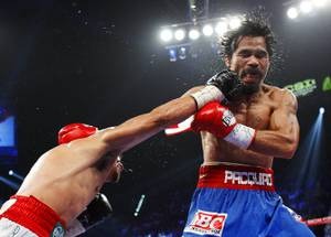 Juan Manuel Marquez, left, of Mexico connects on Manny Pacquiao of the Philippines during their WBO welterweight fight at the MGM Grand Garden Arena Saturday Nov. 12, 2011.