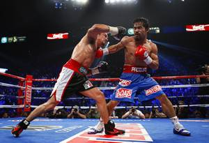 Juan Manuel Marquez, left, of Mexico exchanges punches with Manny Pacquiao of the Philippines during their WBO welterweight fight at the MGM Grand Garden Arena Saturday Nov. 12, 2011.